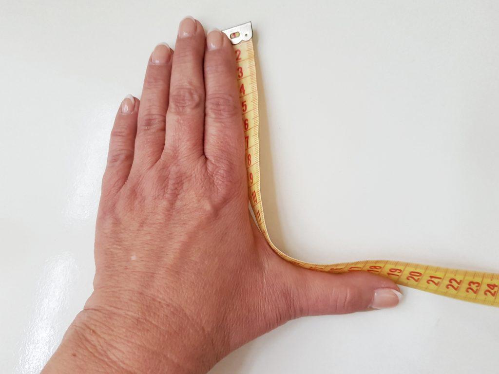 Länge zwischen dem ausgestrecktem Zeigefinger und Daumen messen, ergibt die Mützenhöhe